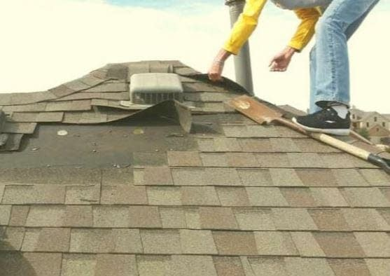 an asphalt roof replacement is being performed by a roofer