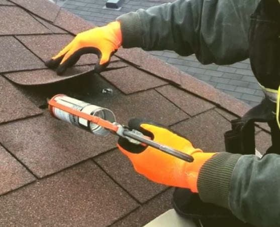 a roofing expert tries to repair a damaged asphalt roofing
